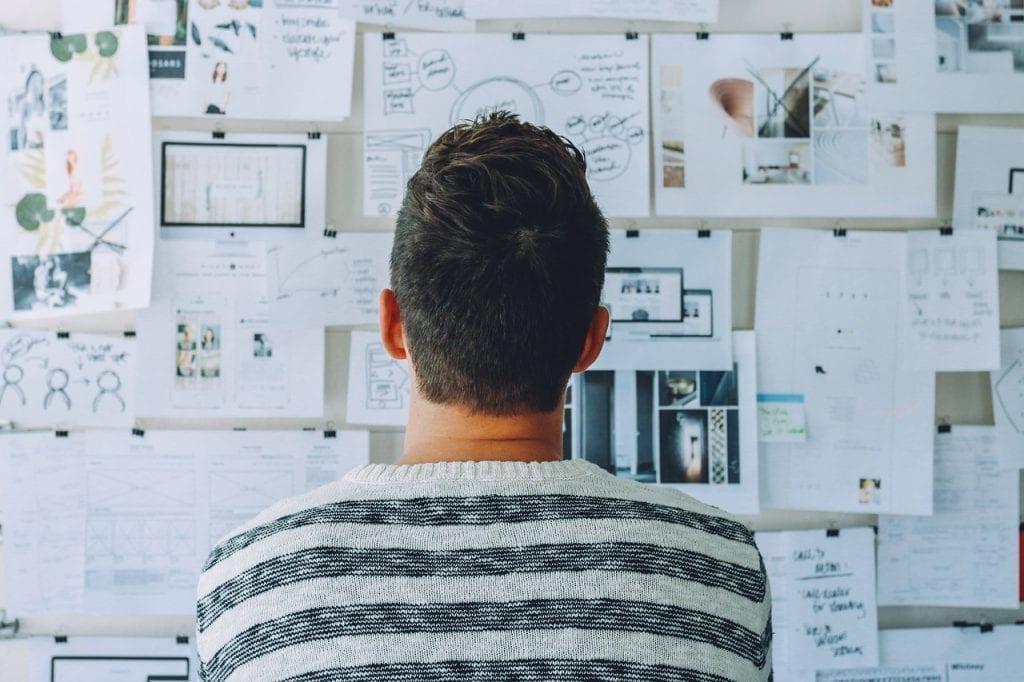 jovem empreendedor encarando um quadro de planejamento com varias notas