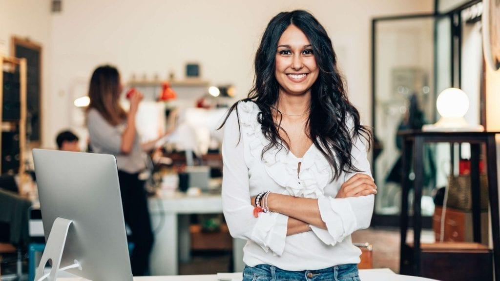 Mulher sorrindo em primeiro plano com escritório ao fundo