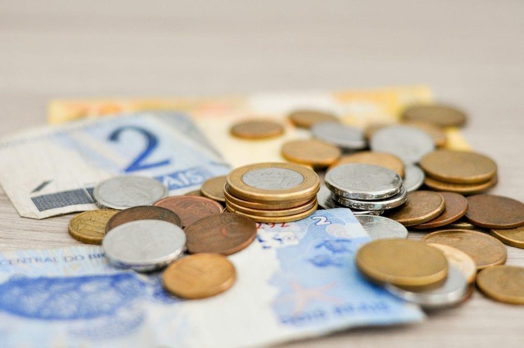 juros altos e varias cedulas com moedas em cima