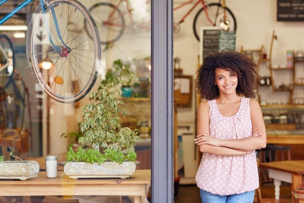 Mulher sorrindo em frente de uma loja de bicicletas