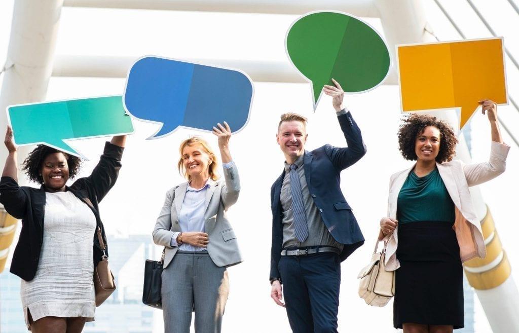 Pessoas empreendedoras sorrindo com plaquinhas de dialogo levantadas para cima