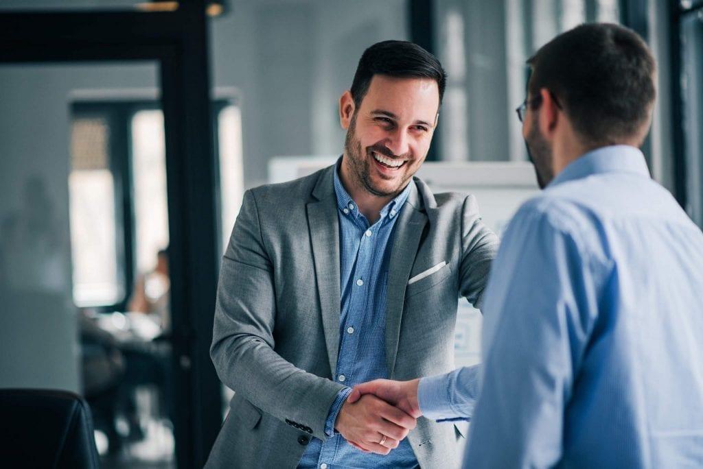 Homem sorrindo apertando a mão de outro sobre vendas realizadas
