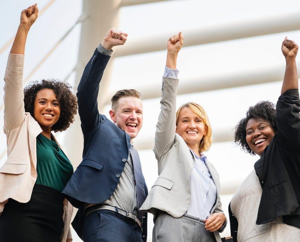 Pesssoas empreendedoras sorrindo com mão para cima e um punho cerrado