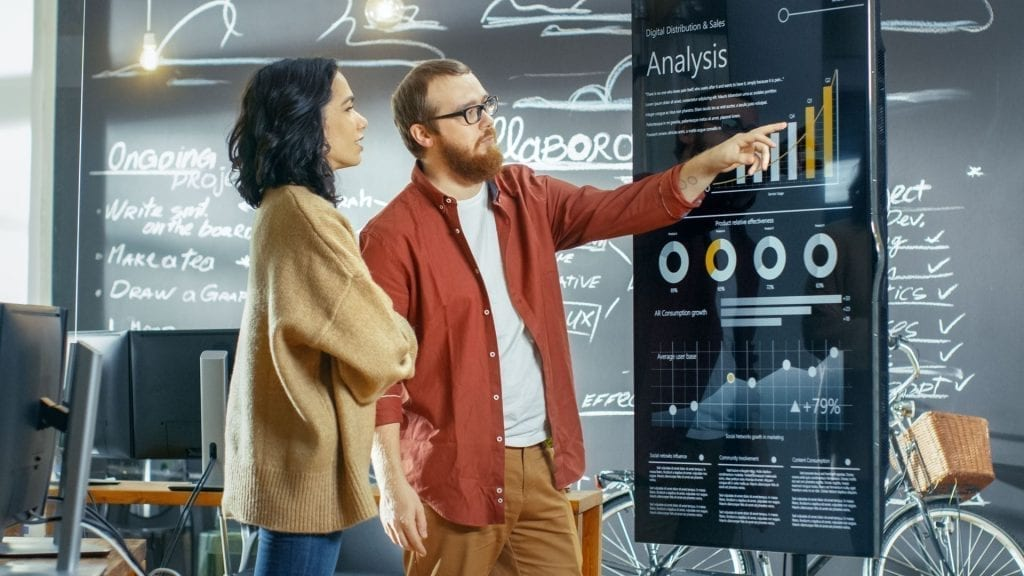 female developer and male statistician use interactive whiteboard presentation touchscreen to look at charts graphs and growth statistics they work in the stylish creative office 1