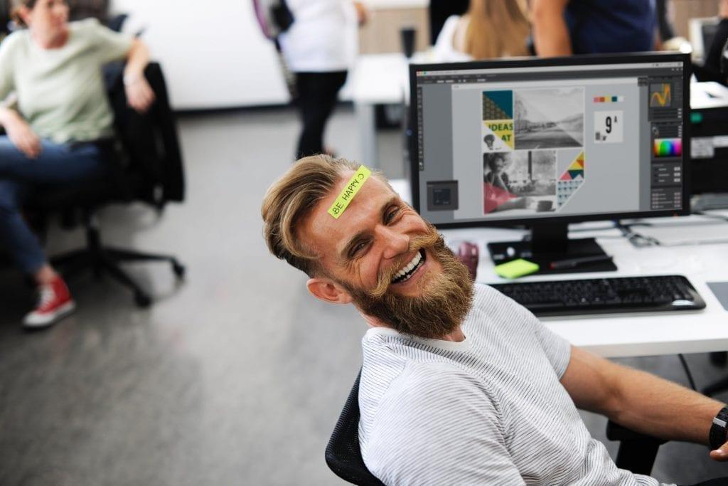 """Rapaz em um escritório sorrindo com a frase em post-it """"be happy"""" na cabeça"""