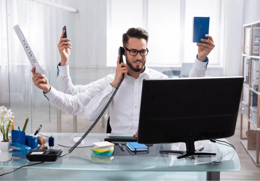 pessoa em frente ao computador com vários braços simulando que ela tem muitas atividades