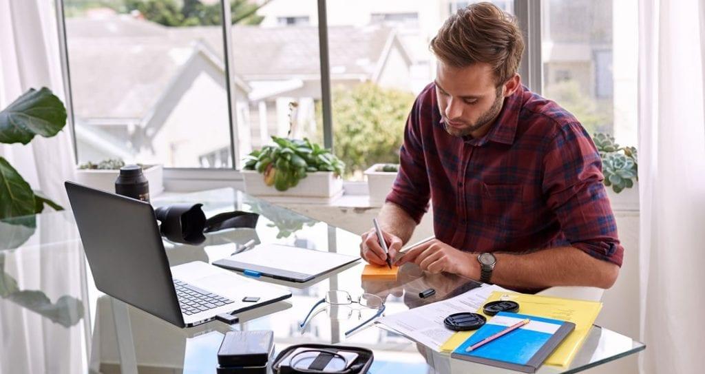 homem trabalhando com bloco de notas e computador