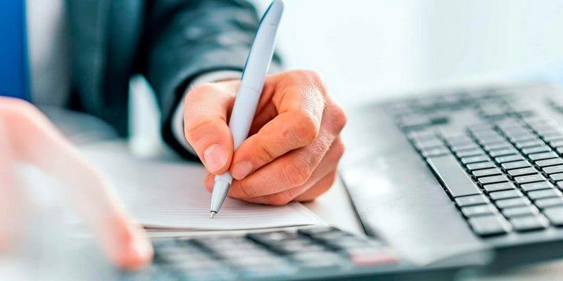 mão fazendo cálculo com caneta no papel