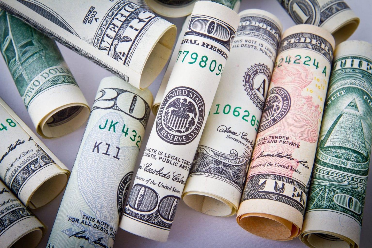 várias notas de dólar enroladas