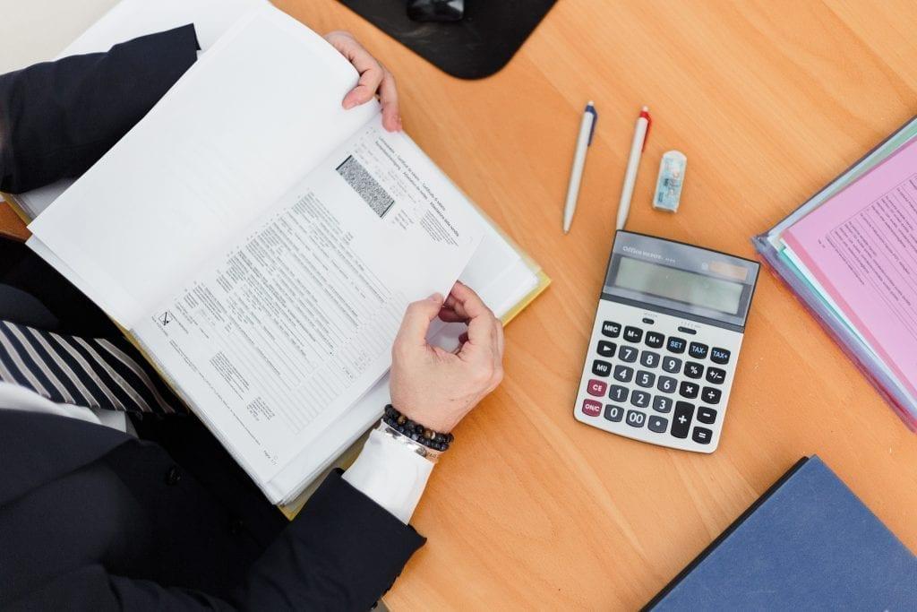 homem com folhas de papel e calculadora