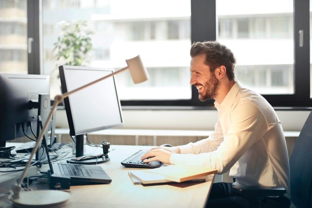 homem na frente do computador sorrindo