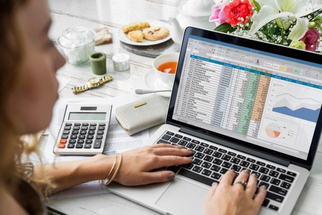 mulher fazedo calculo planilha finanças computador