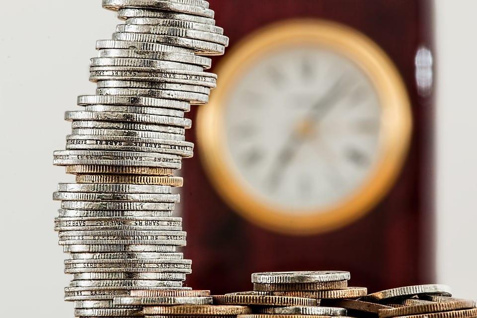 pinha de moedas com um relógio ao fundo