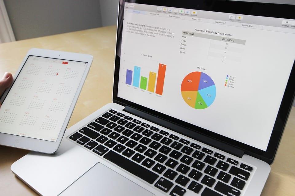 Notebook ligado em cima de uma mesa. Gráficos coloridos aparecem junto a uma mão segurando um tablet